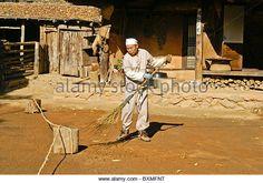 Man sweeping yard, Korean Folk Village, South Korea - Stock Image