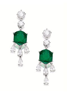 UNIQUE PAIR OF EMERALD AND DIAMOND PENDENT EARRINGS.  Each suspending on a hexagonal emerald weighing 9.62 and 8.00 carats respectively, surmounted by brilliant-cut diamonds, supporting a cascading fringe of pear-shaped diamonds, the diamonds altogether weighing 8.70 carats, embellished to the back by circular-cut diamonds, mounted in platinum.