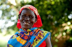 A woman in rural Uganda smiles as the charity: water team arrives in her village.