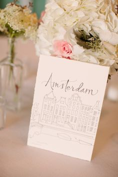 Calligraphy table names with drawings of their fave cities to visit. Paperfinger.