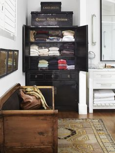 This California ranch house's bathroom has a vintage black lacquer cabinet that stores sweaters. #storageideas