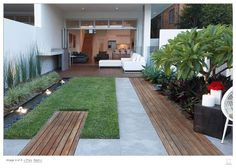 Small back garden design Plants include: ornamental ginger, Mexican lily, Bangalore palms, century plants, variegated mondo and two frangipani trees over rhoeo. Small cape rush along water rill