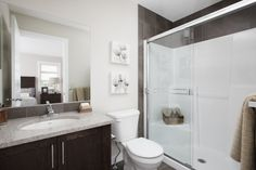 Ensuite with tile flooring, walk-in shower, light granite counters and wood cabinet Light Granite, Tile Flooring, Granite Counters, Walk In Shower, Wood Cabinets, Home Builders, New Homes, Mirror, Bathroom