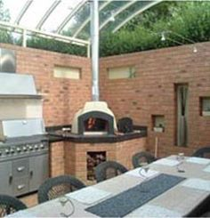 Vesuvio Wood Fired Oven – FVR 100  The perfect fusion of traditional and modern cooking methods, are used in this alfresco dining area, to create a year round retreat that is the height of style.  The wood fired oven and surrounding workspace has been finished with black granite and the flue extension allows the oven to extend through the roof of the alfresco area.