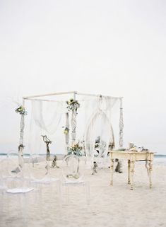 An incredible chuppah and Lucite ghost chairs on the beach.