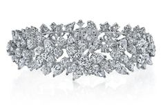Multi-Shape Diamond Scatter Bracelet by Joshua J - A mélange of diamond shapes is scattered along this platinum bracelet, with a mixture consisting of 34 pear shapes, 15 marquise, and 96 round colorless diamonds. Total weight for this platinum medley is 31.26 cts.