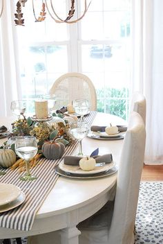 A twist on traditional Fall colors. This tablescape uses steel gray, slate blue and natural accents mixed with pops of silver.  Perfect for fall or a non-traditional thanksgiving table idea. Create a beautiful table with inexpensive dishes and decor available at HomeGoods. Sponsored Pin.