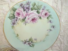Porcelain Plate with Pink Roses and violets by Amy Enright Medina via Flickr. China painting and decorative painting use very similar designs although when working on porcelain; the highlights are wiped out whereas in decorative painting, we add white paint to the brush for the highlights.