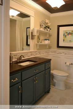 DIY remodeled bathroom with stained wood slat ceiling, mirror with sconces, vanity made from  stock oak cabinets