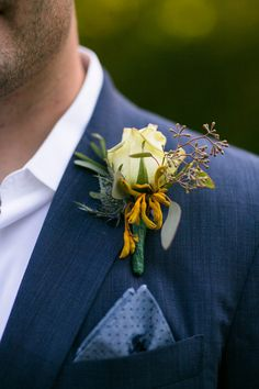 A yellow boutonniere featuring a rose, thistle, seeded eucalyptus and olive leaves complements this groom's navy blue tuxedo. {@marksphotos}