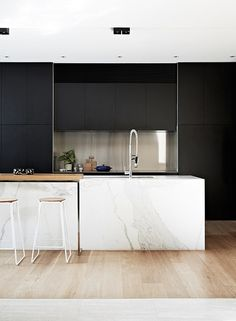 Contemporary kitchen with black cabinets and marble island by David Watson Architect