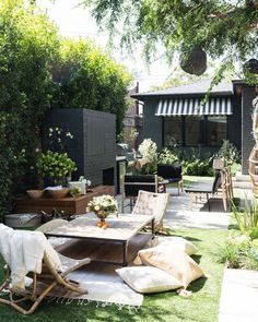 Hello dream backyard design. Love that outdoor fireplace and the black and white boho feel.