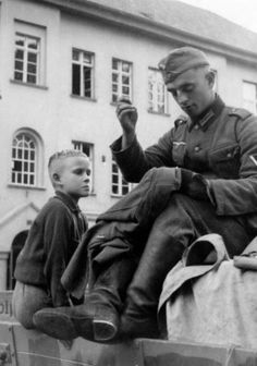 A young Polish boy watches intently as an occupying German Wehrmacht soldier mends a torn uniform