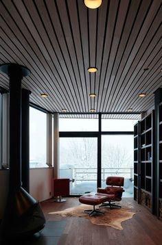 wood slatted ceiling, dark wood stove, hide rug, Eames lounger