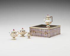 The Royal Collection: Miniature tea serviceCreator: Fabergé (goldsmith) Creation Date:  1896 - 1908. Materials:  Gold, crystal, enamel, ruby Dimensions:  2.4 x 6.4 x 6.4 cm  Provenance:  Belonged to Queen Alexandra Description: Comprising a teapot, hot water pot, sugar bowl and milk jug, this tea set is of gold enamelled in a pale opaque bluish-white, but there is no engine turning on the metal. This deliberately plain enamelling creates the impression that the tea set is made of porcelain.
