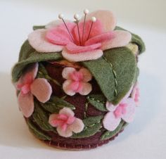 OH what a sweet pink and chocolate flower pincushion. The dusty greens compliment those pinks so well! Love how the pins add to it's beauty