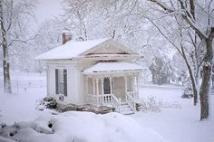 Tiny white house in a blanket of white. This is a picture I would want to wish myself into...following the snow tracks into the front door, lighting the lamp inside and settling into a chair with a good book!