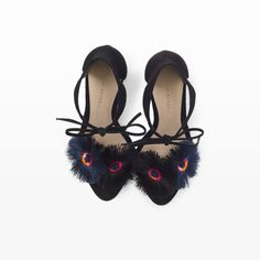 """Loved by fashion editors and celebrities alike, Loeffler Randall's footwear is known for its understated sophistication and downtown-cool aesthetic. This pair of heels in ultra soft kid suede with fringed floral appliques is the fastest way to add a playfully refined sensibility—and comfortable height, thanks to wide heels—to any outfit. Kid suede  3½"""" heel Slip-on style with ankle ties; two fringed and embroidered flo"""