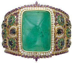AN EMERALD, RUBY, SAPPHIRE AND DIAMOND BANGLE  Centering upon a large sugarloaf cabochon emerald, to the openwork tapering band set with sapphire, emerald, ruby and diamond foliate motifs, mounted in gold