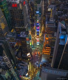 Times Square Manhattan. Ablaze with lights and activity on the 4th of July, as seen from the dramatic perspective of a helicopter at night. Started out as Long Acres Square in the late 1800's, named...