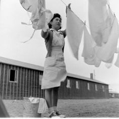 Japanese-American woman hanging laundry at the Heart Mountain Relocation Camp. Heart Mountain, Wyoming, USA, September 1942.