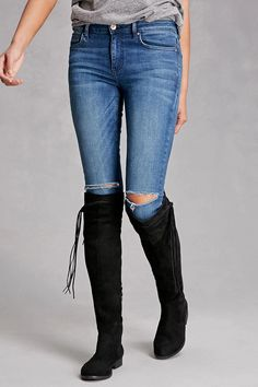 LFL by Lust For Life™ created a pair of faux suede over-the-knee boots featuring a low heel, fringed trim, a crisscross detail at the cuff, and a side zipper closure.