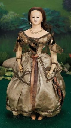 Early French Papier-mache Lady Doll with Original Tacked-on Costume French,circa 1840. Value Points: the early model poupee has beautiful face with fine definition around the mouth,daintily-shaped double chin,and is wearing her original tacked-on silk and velvet gown and slippers. Raised by the Song of the Murmuring Grove: 281