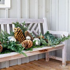 Give your porch bench some holiday spirit with an arrangement of greenery, pinecones, gazing balls, and ornaments. Spray the arrangement with a light dusting of fake snow for extra winter flair./