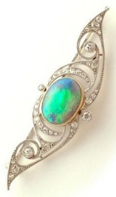 AN ART NOUVEAU OPAL AND DIAMOND BROOCH, BY VEVER, FRENCH, 1900S. Centring an oval natural black opal and further set with diamonds mounted in 18k gold and platinum. Signed VEVER PARIS for Maison Vever. 1.8 x 5.0cm. #Vever #ArtNouveau #brooch