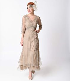 Amorous and fanciful! An alluring dusty sand shade saturates this Edwardian era dress of romantic embroidered tulle and soft muslin. The sweeping silhouette is offset with three-quarter length sleeves and flirty scalloped v-neckline while the delicate she