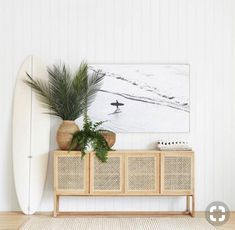 home accessories living room Beautiful beachy vibe with a cane console table in light wood, vertical white shiplap, large wall art, plants, and a surfboard! Living Room Playroom, Living Room Decor, Beach Living Room, Cane Furniture, Living Room Furniture, Beach House Furniture, Coastal Furniture, Ratan Furniture, Console Table Living Room