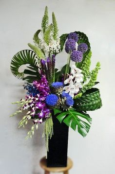 This arrangement took a lot of time! The weaving of the grasses, etc.but what a gorgeous arrangement! I might have to replace the bright blue with something a little less obnoxious Tropical Flowers, Tropical Flower Arrangements, Flower Arrangement Designs, Large Flowers, Silk Flowers, Flower Designs, Ikebana, Church Flowers, Funeral Flowers