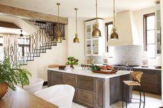 Mediterranean kitchen features four Chart House Mini Yoke Pendants in Hand-Rubbed Antique Brass ...