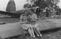 Schoolgirls sit on part of a Nazi bomber which crashed near their farmhouse.