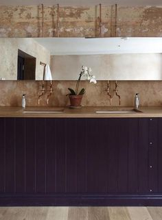The modern baths feature exposed copper plumbing fixtures and cabinetry painted in deep shades of purple.