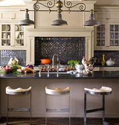 English Country Kitchen:   Exposed wooden ceiling beams, slatelike granite countertops, and industrial-style stools with butcher-block seats create charm in the English country-style kitchen. The expansive island provides plenty of space to cook and gather.