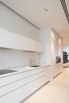 Kitchen minimalist - integrated fridge, no handles, rear sliding door splash back for extra appliance and condiment storage