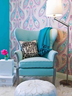 This tween girl's bedroom sitting area features a vintage chair reupholstered in a blue houndstooth, a white leather pouf ottoman and a feminine paisley wallpaper.