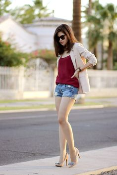 Adriana Gastellum is wearing a nude blazer from Chicwish, oxblood dress worn as a top from MotelRocks, denim shorts from Sheinside, nude bow...