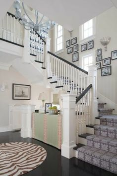 Dark stained treads and bannister against light/white spindles & ballustades - also love the gallery art up the stairs.