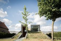This wedge-shaped house has a sloping green roof facing the street