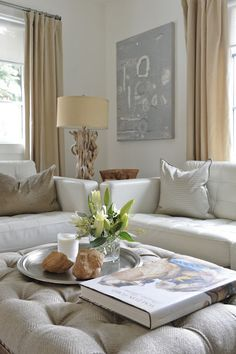 Living room - Muted palette with a natural driftwood base table lamp, tufted top ottoman & a white leather sofa.  All the pieces work with each other...lovely.