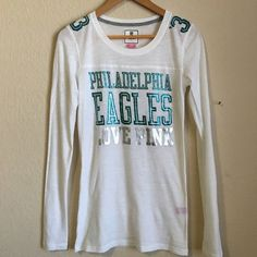 """Victoria's Secret Pink Philadelphia Eagles Shirt Victoria's Secret Pink Philadelphia Eagles Shirt. Jersey NWOT!  Never been worn. Super soft and lightweight cotton/modal blend. Long sleeve. Sexy athletic fit.  Bust 30"""", waist 28"""", length 27"""". #sporty, #sport, #fan, #game shirt, #vs, #tee, #t-shirt, #tee shirt. Victoria's Secret Tops Tees - Long Sleeve"""