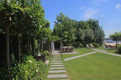 tuin tuinontwerp tuinarchitect hovenier hoveniersbedrijf tuinaanleg beplanting beplantingsplan onderhoud tuin aan het water stapstenen in gras zeilbootje bootje
