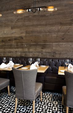 Love grey upholstered chairs with black banquette and reclaimed wood and geometric tiles