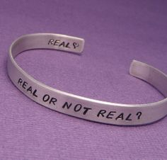 Hunger Games Inspired ~ Real Or Not Real ~ A Double Sided Hand Stamped Aluminum Bracelet, via Etsy.