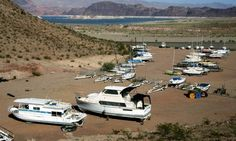 Lake Mead is seen in the distance behind boats in dry dock near the Lake Mead Marina in Nevada.