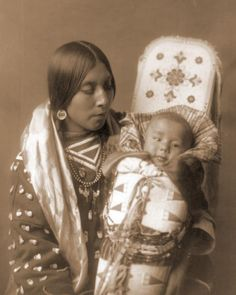 American Indian Mother holding her Child. It was taken in 1908 by Edward S. The image shows a Portrait of a Native American woman in a half-length, seated, facing right, position holding her baby in a beaded cradleboard. Native American Beauty, Native American Photos, Native American History, Native American Indians, Crow Indians, American Crow, American Baby, American Life, World Cultures