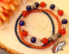 You will receive a lot of compliments on this beautiful stacked bracelet as you cheer on the Denver Broncos! This is a stunning handmade piece carefully crafted by Blossom with Hope. Shades of navy blue and orange with delicate accents of hematite, crystal and silver tone beads. Product Details: Style ~ Beaded, Stretch. Colors ~ Shades of navy blue and orange. Accents ~ Hematite, Crystal, Silver tone beads, Official NFL charm