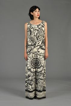 1970s graphic jumpsuit by Mr Dino. Black + ivory illustration style print featuring a prowling tiger at the edge of a rippling stream covered by various kinds of flowering water lilies.